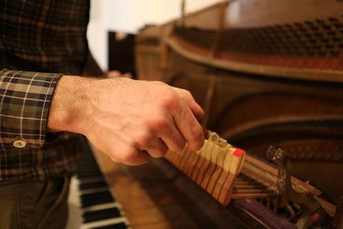 Andrew Wedman tuning the Bass Piano. Photo by Ekaterina Usmanova