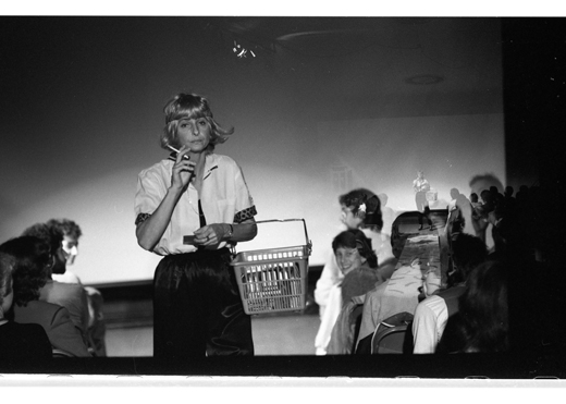 "A double exposed image of Anna Banana Performing ""Why Banana?"" in the Grand Luxe Hall at Western Front, 1982"