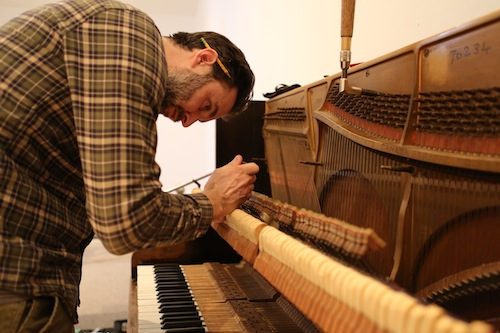 Andrew Wedman studiously tunes the bass piano. Photo by Ekaterina Usmanova