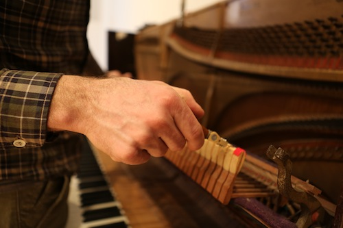 Andrew Wedman tuning the Bass Piano. Photo by Ekaterina Usmanova