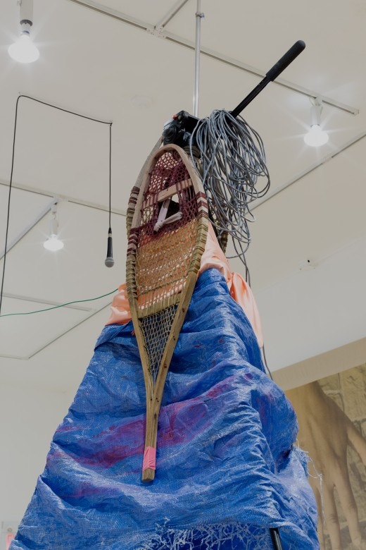 "Duane Linklater, ""apparatus for the dissemination of Indigenous ideas and sounds into the air"", tripod, radio transmitter, hand dyed snowshoes, tarpulin, fabric, string, stone, tape, speaker, paint, wiring, dimensions variable, Western Front, 2017. Photo courtesy of Dennis Ha."
